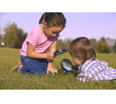 Picture of a girl and boy looking through magnifying glasses
