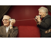 Picture of a man and a woman using two cans and a string as a telephone